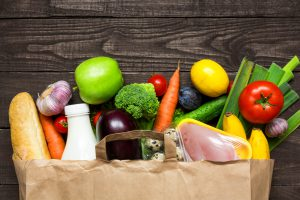 Full paper bag of different health food on rustic wooden background. Top view. Flat lay