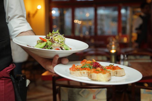 Lexington Restaurant Week new restaurants: a server caring 2 white plates with food on it