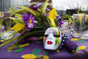 Mardi Gras mask with yellow, purple, and green and purple flowers