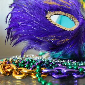 Mardi Gras mask and beads with purple, yellow, and green