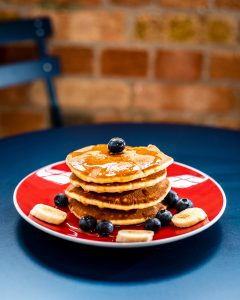 Brunch: stack of pancakes with bananas, blueberries, and syrup