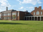 Paul Miller Ford: view of a high shool building with green grass and blue skies