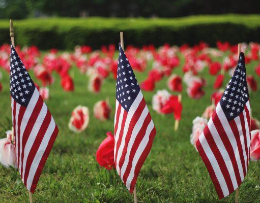 Labor Day: three American Flags in the ground with flowers behind