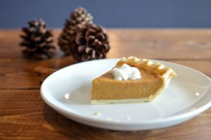 Thanksgiving: piece of pumpkin pie on a white plate