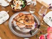 Thanksgiving: turkey on a silver platter with glasses and salad around it on a wooden table