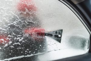 iced window from inside car cleaning snow storm