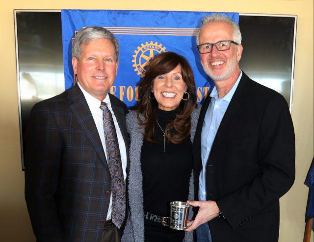 humanitarian: two men and a woman holding an award and smiling at the camera